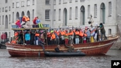 Amnesty International activists protest against the ongoing migrant crisis with a boat filled with mannequins wearing life vests outside the Maritime Museum, rear, during an informal meeting of EU Justice and Home Affairs ministers at the Maritime Museum