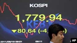 A currency trader passes by a screen showing the falling Korea Composite Stock Price Index (KOSPI) at the foreign exchange dealing room of the Korea Exchange Bank headquarters in Seoul, August 19, 2011