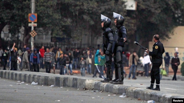 Riot police try to stop clashes and ask protesters, opposing Egyptian President Mohamed Mursi, to back away along Qasr Al Nil bridge, which leads to Tahrir Square in Cairo, Mar. 7, 2013.