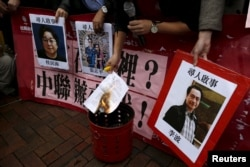 FILE - A pro-democracy activist burns a letter next to pictures of missing staff members of a publishing house and bookstore outside the Chinese liaison office in Hong Kong, Jan. 3, 2016.