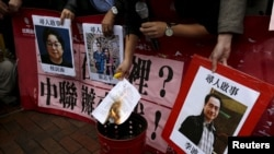FILE - A pro-democracy activist burns a letter next to pictures of missing staff members of a publishing house and bookstore, including Gui Minhai, owner of Mighty Current, outside the Chinese liaison office in Hong Kong, Jan. 3, 2016.