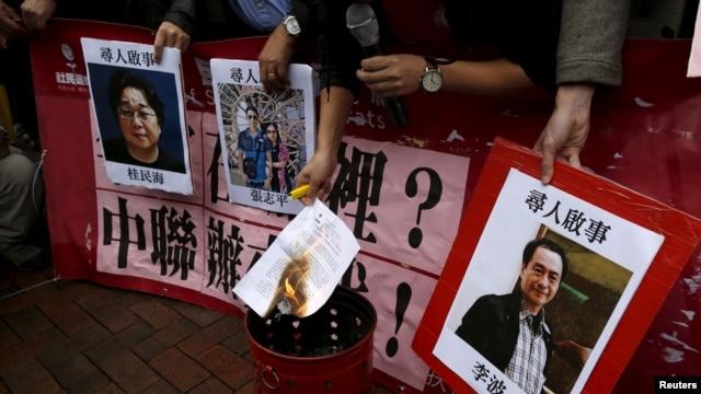 香港示威者在中联办外面要求调查铜锣湾书店职工和店主失踪案, 右一是李波照片。(2016年1月3日)