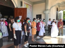 Para petugas gereja bersiap memeriksa suhu tubuh kepada umat yang hendak memasuki gedung gereja Katedral Ruteng, Nusa Tenggara Timur pada saat upacara penahbisan Uskup Ruteng, Kamis, 19 Maret 2020. (Foto: Pastor Steven Lalu)