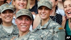 FILE - Army 1st Lt. Shaye Haver (center) and Capt. Kristen Griest (right) pose with other female West Point alumni after an Army Ranger school graduation ceremony at Fort Benning, Ga. Haver and Griest became the first female graduates of the Army's rigorous Ranger School, Aug. 21, 2015.