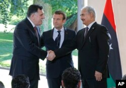Libya's Prime Minister Fayez al-Sarraj of the U.N.-backed government (L), and General Khalifa Hifter of the Egyptian-backed commander of Libya's self-styled national army shake hands as France's President Emmanuel Macron stands between after a declaration at the Chateau of the La Celle-Saint-Cloud, west of Paris, France, July 25, 2017.