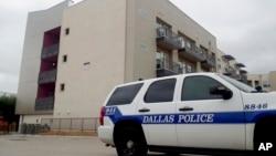 """Sebuah mobil polisi Dallas diparkir di dekat gedung apartemen South Side, lokasi terjadinya """"penembakan hingga tewas"""" di Dallas, Texas, Senin (10/9)."""