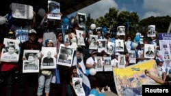 """Nicaraguan expats living in Costa Rica hold pictures of people killed in riots or imprisoned as they take part in the """"Caravan for Liberty and Justice"""" to protest against the government of Nicaraguan President Daniel Ortega, in La Cruz, Costa Rica, on the"""