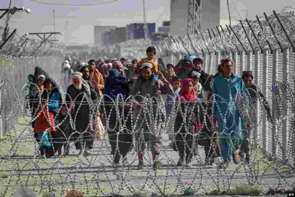 Afghans walk along fences as they arrive in Pakistan through the Pakistan-Afghanistan border crossing point in Chaman, following Taliban's military takeover of Afghanistan.