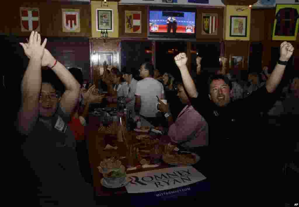Mariella Roque et Jorge Palamino de Miami, partisans du candidat Mitt Romney, applaudissent en regardant le débat Obama-Romney à la télévision