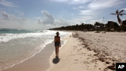 A woman walks along the beach in Tulum, Mexico.
