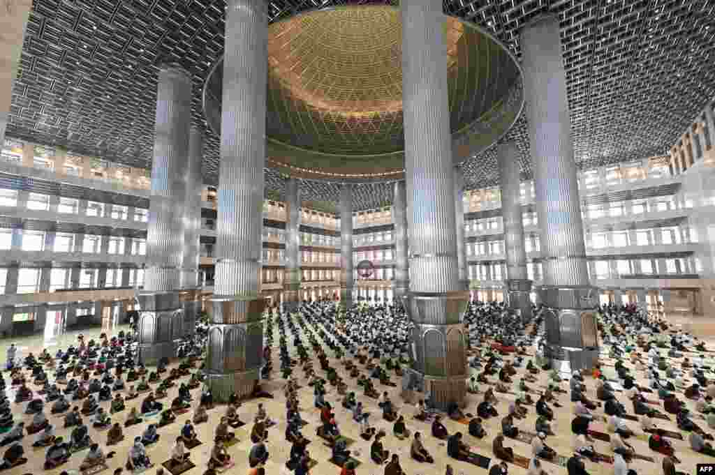 Muslim people conduct Friday prayers with physical distancing at the Istiqlal mosque in Jakarta, Indonesia.