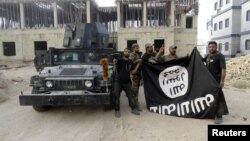 FILE - Iraqi security forces hold an Islamic State flag upside down in Anbar, Iraq, July 26, 2015, following the liberation of the city from IS militants. Pushing IS militants from their home turf will open a whole new challenge, experts caution.