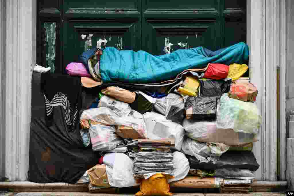 A homeless man sleeps on a pile of plastic bags and newspapers under a porch in Rome, Italy.