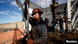 Roughneck Brian Waldner is covered in mud and oil while wrestling pipe on a True Company oil drilling rig outside Watford, North Dakota, October 20, 2012. Thousands of people have flooded into North Dakota to work in state's oil drilling boom. REUTERS/Jim