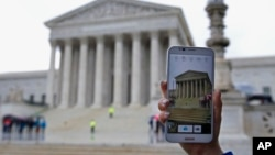 FILE - A Supreme Court visitor takes pictures with her cell phone outside the Supreme Court in Washington.