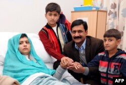 A handout picture received from the Queen Elizabeth Hospital/University Hospitals in Birmingham shows Pakistani schoolgirl Malala Yousafzai sitting on her bed and holding hands with her brothers Khushal Khan (3rd R), Apal Khan (R), and father Ziauddin Yousufzai at the hospital in Birmingham, England, October 25, 2012.