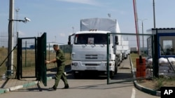 FILE - A Russian border guard opens a gate in Russia's Rostov-on-Don region, bordering Ukraine, Aug. 22, 2014.