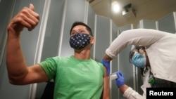纽约市西奈山医院的Tommy Wong医生在接种辉瑞新冠病毒疫苗时伸出大拇指。(2020年12月15日)