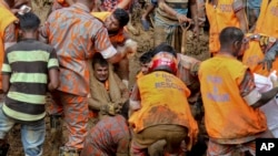 Rescuers pull out the dead body of a victim after Tuesday's massive landslide in Rangamati district, Bangladesh, June 14, 2017.