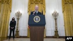 Presidenti Biden duke njoftuar arritjen e 100 milionë injektimeve të vaksinës, ndërsa në sfond qëndron Nënpresidentja Harris (Dhoma Lindore e Shtëpisë së Bardhë, 18 mars 2021)