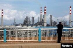 Seorang pengunjung mengamati kilang minyak China National Offshore Oil Corporation (CNOOC) di Huizhou, provinsi Guangdong selatan China, 28 Juli 2009. (Foto: dok)