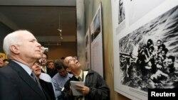 Thượng nghị sĩ Mỹ John McCain nhìn bức ảnh lúc ông bị bắt trên hồ Trúc Bạch trong chuyến thăm nhà tù Hỏa Lò tại Hà Nội hồi tháng 4, 2009.