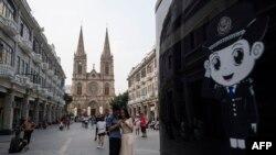 2018年9月22日,中国游客在广东省广州市的圣心大教堂(也称为耶稣圣心大教堂或石狮天主教堂)前拍照。旁边是警察的漫画形象。