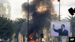 Smoke rises from fire left after clashes between security forces and demonstrators in Tunis, Tunisia, 14 Jan 2011