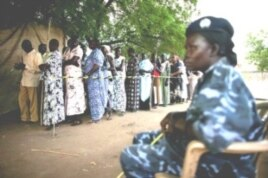 A police officer watches as women queue to vote during the recent referendum on South Sudan's independence. (April 2011)