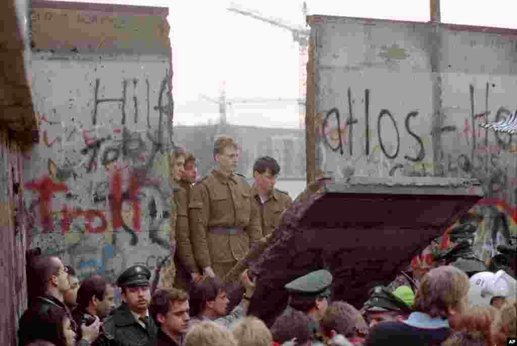 و بخشی از دیوار برلین که مقابل دروازه براندنبورگ جدا شد. سربازان آلمان شرقی در آنسوی دیوار نظارهگر برچیده شدن دیوار بودند