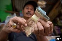 Seorang penjual makanan ringan menghitung uang hasil penjualannya, Jakarta, 20 Februari 2020. (Foto: AFP)