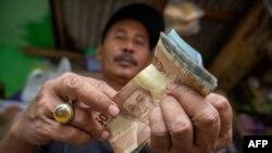 Seorang penjual makanan ringan menghitung uang hasil penjualannya yang jauh berkurang akibat pandemi Covid-19 di Jakarta. (Foto ilustrasi: AFP)