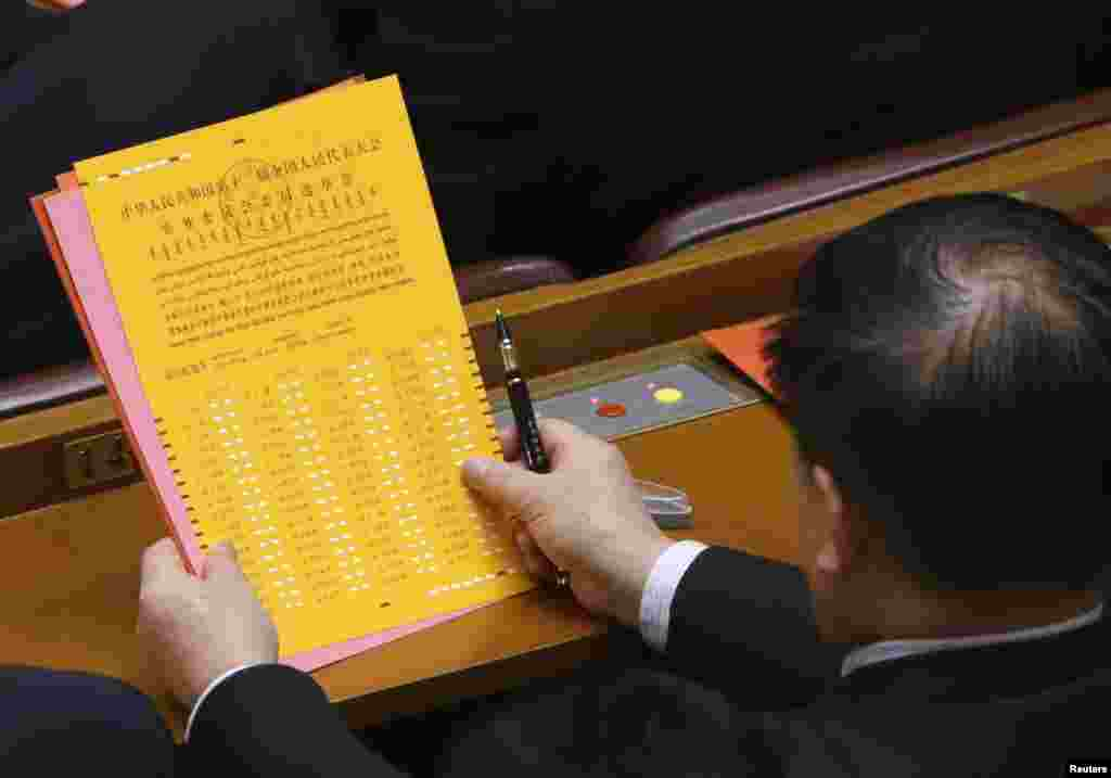 A delegate looks at a ballot during the fourth plenary meeting of the National People's Congress (NPC) at the Great Hall of the People in Beijing, March 14, 2013.