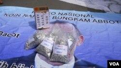 Spanduk bergambar PM Australia Tony Abbott ditutupi bungkusan belasan ribu koin rupiah di Kedubes Australia Jakarta (10/3). (VOA/Andylala Waluyo)