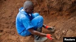 Mfanyakazi wa Burundi kutoka katika Kamisheni ya Ukweli na Suluhu akitoa fuvu la mtu aliyekuwa hajatambulikana kutoka katika kaburi la watu waliozikwa pamoja nchini humo. REUTERS/Evrard Ngendakumana - RC21PE9DJA9D