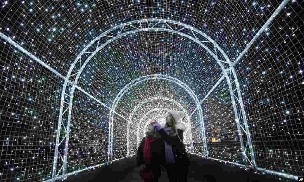 영국 런던의 큐 왕립식물원을 방문한 관람객들이 성탄절을 맞아 설치된 빛의 터널을 지나고 있다.