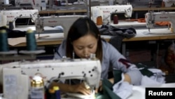 FILE - A woman works in a small-sized factory producing clothes and hats, in which more than half of its production line has stopped its operation because of a downturn in its business at the Qingyundian industrial zone in Beijing.