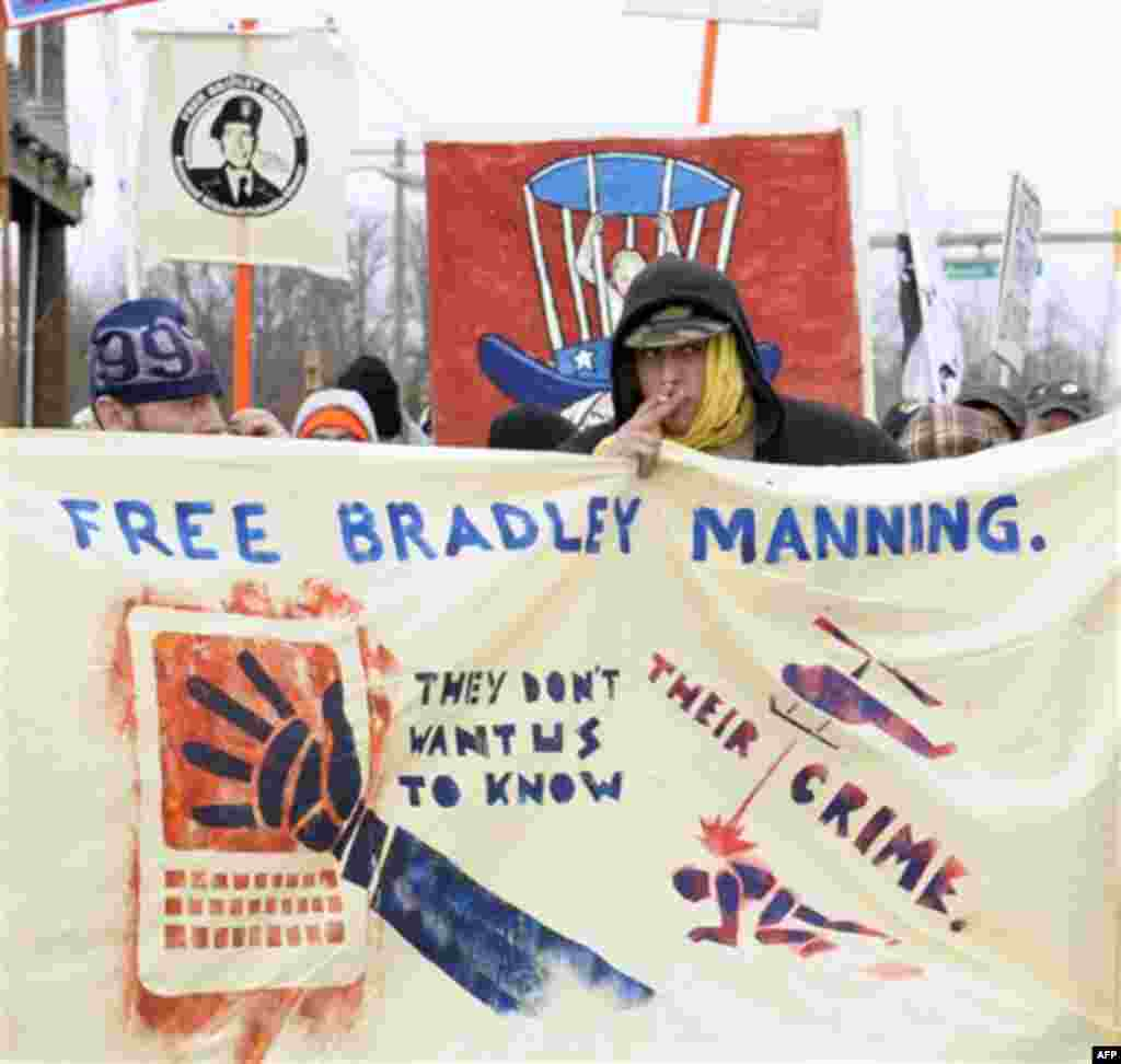 Protestors supporting Pfc. Bradley Manning march outside the gate of Ft. Meade, Md., Friday, Dec. 16, 2011, where Manning will be attending a hearing to determine if he will be court martialed. (AP Photo/Susan Walsh)