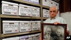 Jack Goins poses with a photo dated to have been taken in 1898 of his great-great grandparents found through genealogical research, May 23, 2012.