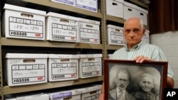 Jack Goins poses with a photo dated to have been taken in 1898 of his step-great-great grandfather George Washington Goins, who died in 1917, left, and great-great grandmother, Susan Minor-Goins who died in 1913 at the Hawkins County Archives Project buil