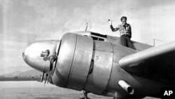 FILE - American aviator Amelia Earhart waves from the Electra before taking off from Los Angeles, California, March 10, 1937.