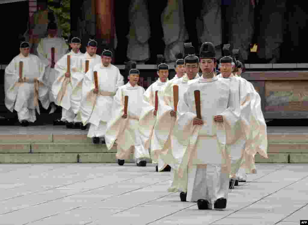 "Shinto priests walk out from the outer shrine after they administer a Shinto rite ""Kiyoharai"" on the first day of the four-day autumn festival at the Yasukuni shrine in Tokyo, Japan."