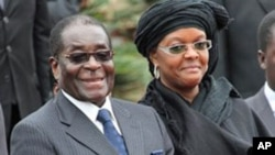 Zimbabwean President Robert Mugabe and his wife Grace at the 2010 funeral of his sister, Sabina