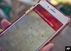 A mobile phone customer looks at an earthquake warning application on their phone in Los Angeles, Jan. 3, 2019. Los Angeles has released the app that could give county residents precious seconds to drop, cover and hold on in the event of a quake.