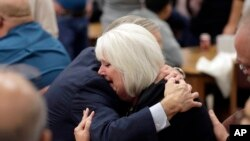 Texas Gov. Greg Abbott, left, hugs a woman as he visits with family and victims before a vigil, Nov. 8, 2017, in Floresville, Texas. A man opened fire inside a church in the small South Texas community of Sutherland Springs on Sunday, killing 26 wounding 20.