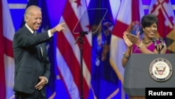 Roslyn M. Brock (R), who chairs NAACP's National Board of Directors applauds as U.S. VP Joe Biden is introduced at their convention, Houston, Texas, July 12, 2012.