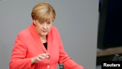 German Chancellor Angela Merkel gestures as she delivers the government's declaration on current refugee crisis at the lower house of parliament Bundestag in Berlin, Sept. 24, 2015.