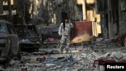 A Free Syrian Army fighter talks on a mobile phone as he stands on the rubble of damaged buildings in Deir al-Zor, eastern Syria, Nov. 12, 2013.
