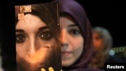 "A Libyan woman holds a pamphlet, which reads ""Together to end the violence against women"" during a gathering in Benghazi Nov. 25, 2012."
