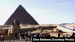 FILE - Tourists are gathering around the Sphinx, which guards the Great Pyramid of King Cheops at the Giza necropolis just outside Cairo, Egypt. (D. Bekheet/VOA)